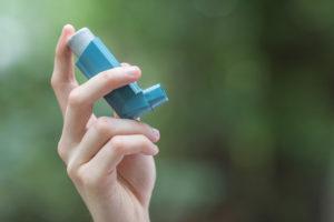 Asthma medecine inhaler holded by a man