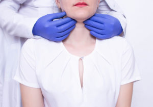Woman getting her adenoids checked by doctor