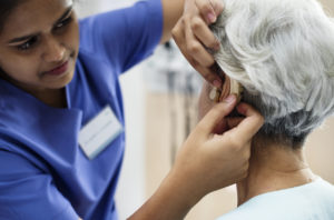 Hearing loss specialist helping woman