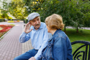 Elderly man tries to hear his spouse. The life of retirees