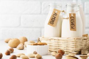 Different nut milk in bottles - almond, cashew and ingredients