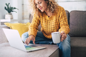 Woman with cup of coffee and typing a Google review for a doctor
