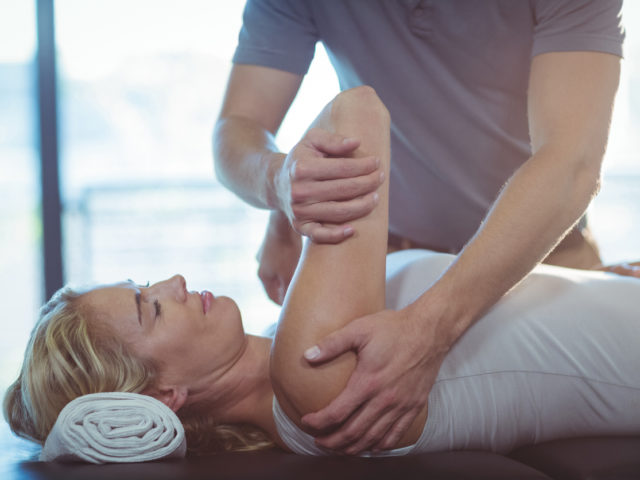 Woman getting her shoulder stretched