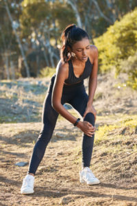 a young woman experiencing knee pain while working out in nature